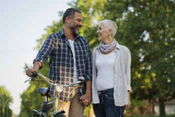 Mature couple walking together with bicycle
